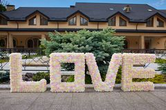 Word Love made of paper flowers outdoors. Symbol of true feelings. stock image