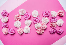 Word love made of paper roses, decorations for Valentine's Day  paper white rustic background top view close up Royalty Free Stock Photo