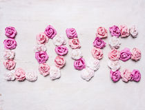 Word love made of paper roses, decorations for Valentine's Day  wooden white rustic background top view close up Stock Photography