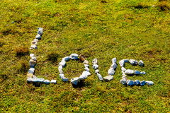 Word love made of pebble stones on mountain meadow. Stock Image