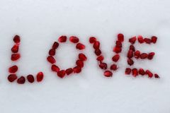 Word Love made of pomegranate seeds on white snow. stock image
