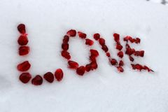 Word Love made of pomegranate seeds on white snow. royalty free stock photos
