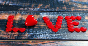 The word LOVE made of red candies and heart Stock Photos