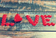 The word LOVE made of red candies and heart Stock Image