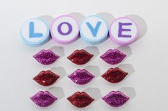 The word love made from rounded erasers and little red and purple lips. Against white background. Valentines Day decoration stock image