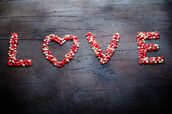 Word Love made with small candy hearts, pink, red, white colors, on dark background. Valentine`s day concept. Top view Stock Images