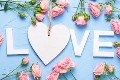 Word love made from white wooden letters, white heart and pink r Stock Photo
