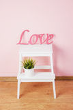 Word love made in wood, pink colored, with green plants Royalty Free Stock Image