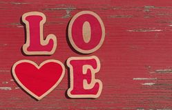 Word love made of wooden letters. On red shabby wooden background royalty free stock photo