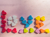 Word Love with multicolored hearts shaped on pink background Stock Image