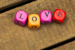 Word love on multicolored wooden cubes on wood Stock Image