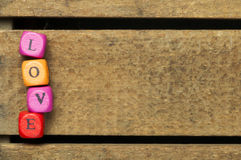 Word love on multicolored wooden cubes on wood Stock Images