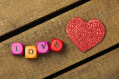 Word love on multicolored wooden cubes on wooden background Stock Photos