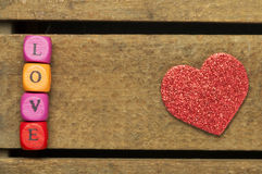 Word love on multicolored wooden cubes on wooden background Royalty Free Stock Images