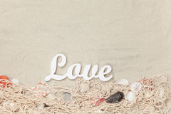 Word Love and net with shells Royalty Free Stock Photo