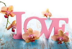 Word love. With orchid on the  wooden blue background Stock Photo