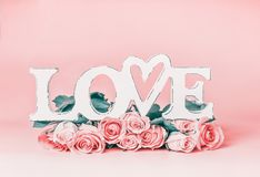 Word LOVE on pastel pink background with roses bunch, front view. Creative female holidays layout Royalty Free Stock Photography
