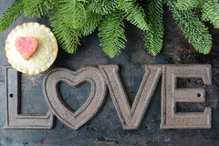The Word Love and A Pie Cupcake Part of Tree On Rustic Metal Bac Stock Image