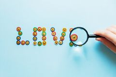 Word love from pins collection of stationery multicolored buttons under magnifier love theme, close up stock image
