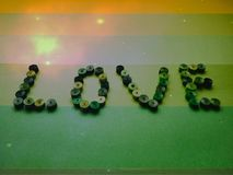 The word love from paper tapes on a green background stock photography