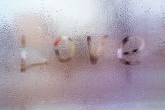 The word Love , rain or water drops on window glasses. royalty free stock image