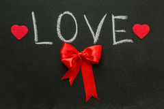 The word love and red bow on the chalkboard Stock Photo