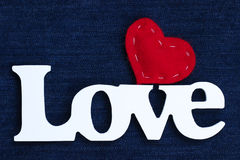 The word Love with red heart on blue denim background. Wood Love text with red fabric stitched heart on blue denim texture backdrop Stock Photo