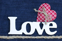The word Love with red heart and rope border on denim background. Wood Love text with red checkered heat with rope bow and rope braid border on blue denim royalty free stock photography