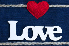 The word Love with red heart and rope border on denim. Wood Love text with red fabric heart and rope border on blue denim texture backdrop royalty free stock photo