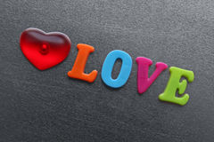 Word love with red heart spelled out using colored fridge magnets Stock Photography