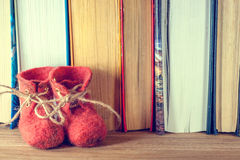 The word love, red shoes, and a lot of hearts on a background of books on a wooden table. Royalty Free Stock Photo