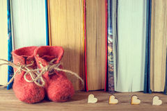 The word love, red shoes, and a lot of hearts on a background of books on a wooden table. Stock Photos