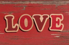 Word love on red wooden board. Word love on old red wooden board stock images
