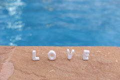 Word Love on the rock and water Stock Images