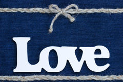 The word Love with rope border and bow on denim. Wood Love text with braided rope border with bow on blue denim textured backdrop royalty free stock images