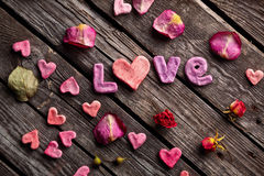 Word Love with rose petals and small heart Stock Photography