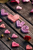 Word Love with rose petals and small heart Royalty Free Stock Images