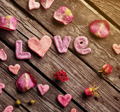 Word Love with rose petals and small heart Stock Image