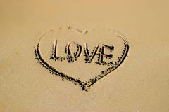 Word love and shape of heart written on sand at the beach by the sea, symbol of love, summer time. Stock Photo