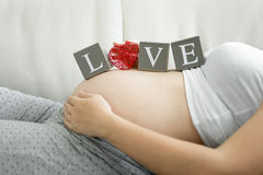 Word Love spelled on blocks on pregnant women tummy Royalty Free Stock Images