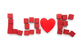 Love Spelled Out. The word love spelled out in blocks and a heart falling apart Stock Photos