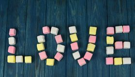 Word love from sweet multicolored marshmallow. On a wooden background of blue color Stock Photography