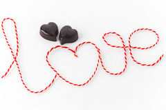 Word love with two chocolate hearts. Word love written with red and white treads with two chocolate hearts against white background Stock Image