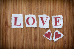 Word Love and two paper hearts on wooden texture background Stock Photo