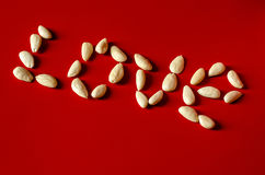 The word LOVE uploaded almonds on a red background. The word LOVE uploaded cleaned almond kernels on a red background Stock Image