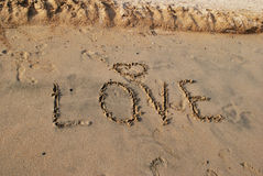 Word LOVE on wet sand Stock Photos