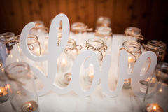 The word LOVE on white cloth around burning candles. Handmade. Scenery Stock Images