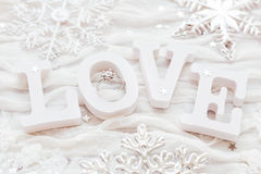 Word LOVE on white fabric background with engagement diamond ring Royalty Free Stock Image