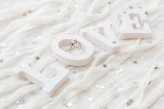 Word LOVE on white fabric background with engagement diamond ring Stock Photo