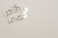 The word with love with white flowers on the beach surface backgr Royalty Free Stock Photos